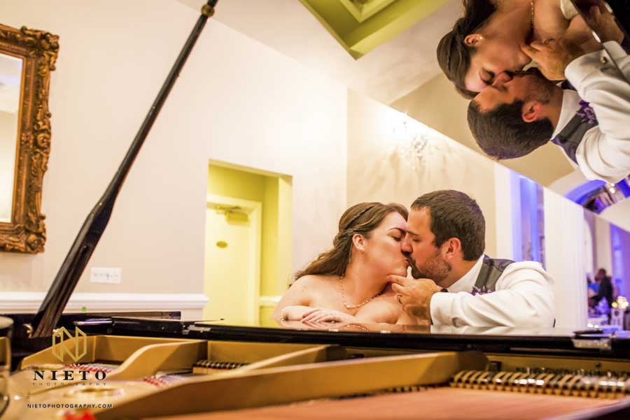 bride and groom kissing while sitting at a piano and their reflection in the top