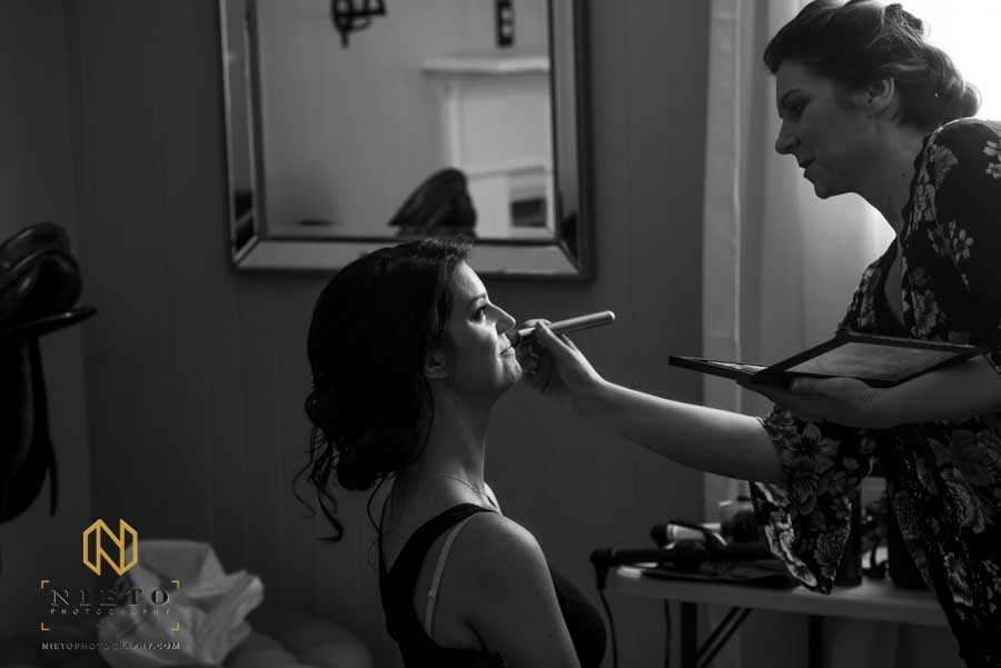 black and white image of a makeup artist putting makeup on a bridal model
