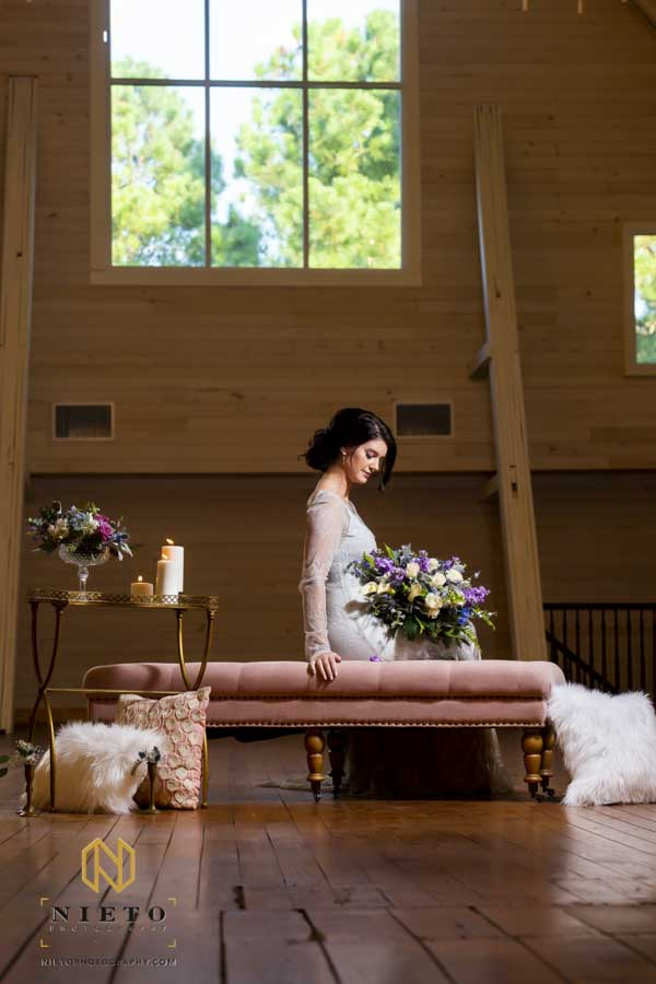 a woman posing for her Wakefield Barn Bridal Portraits while sitting on a pink couch