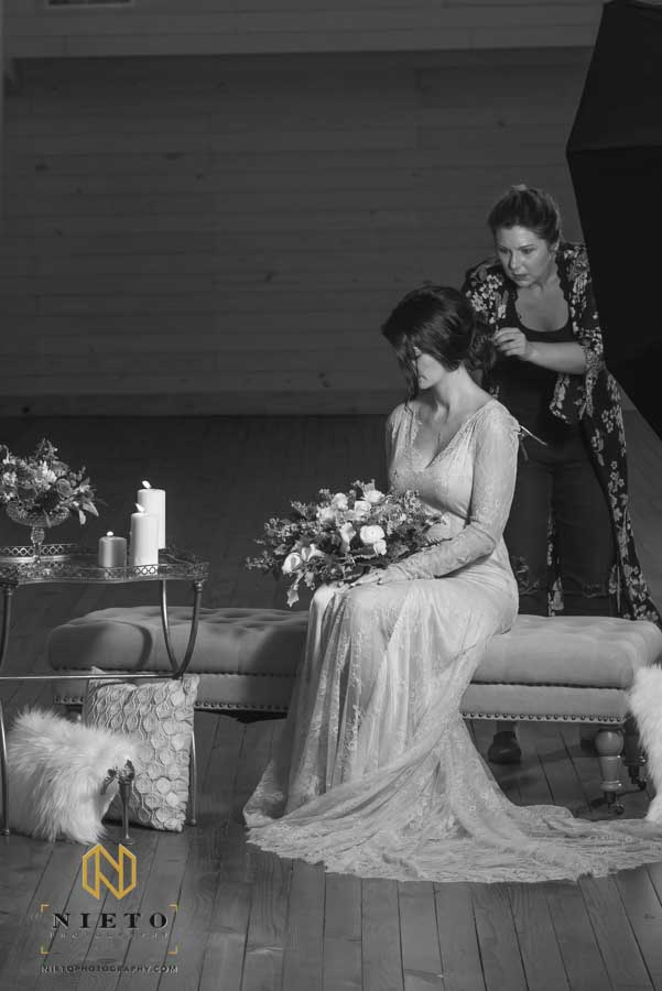black and white image of the hair stylist adjusting the brides hair