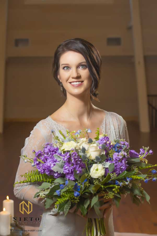 portrait of a bride holding a purple and blue flower bouquet