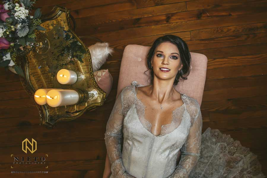 bride laying down on a pink couch with a table and candles beside her