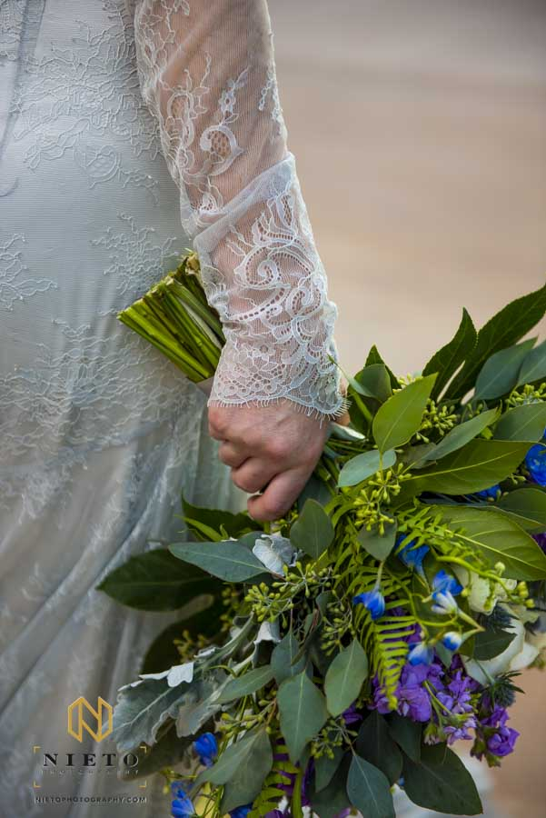 brides hand holding the bridal bouquet while she wears a blue dress
