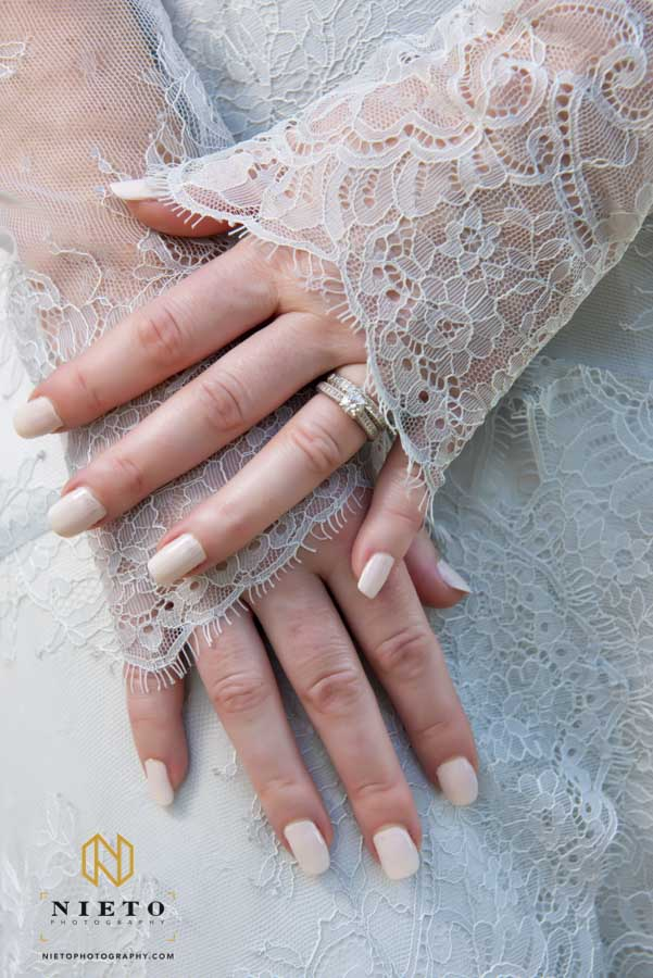 closeup image of the brides a hands and the sleeves of her gown