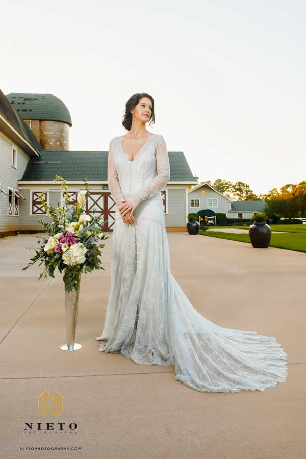 bride standing near a tall floral vase outside of the Historic Wakefield Barn