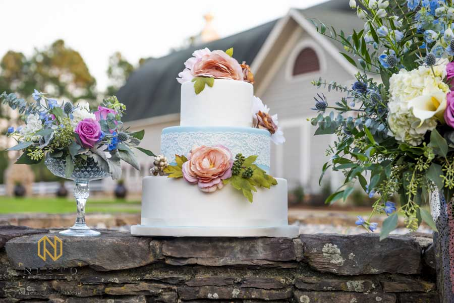 cake on a stone wall in-between flowers
