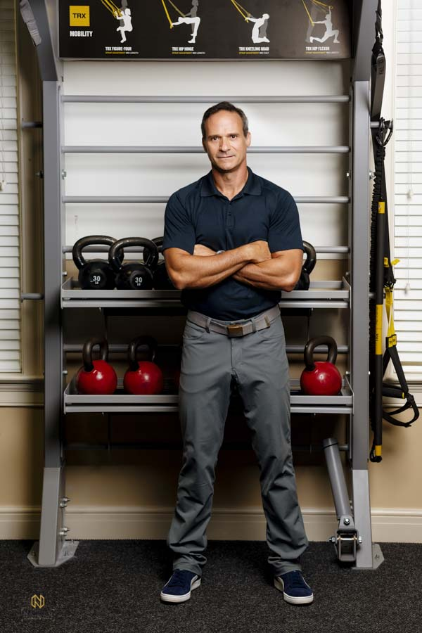 Man posing with his arms crossed in front of a weight rack