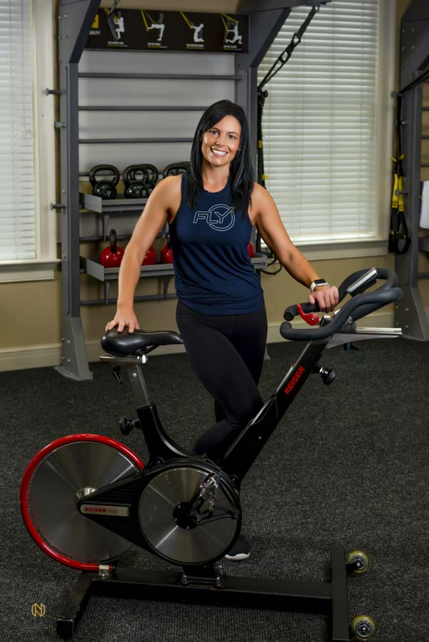 woman posing with a fly wheel bike