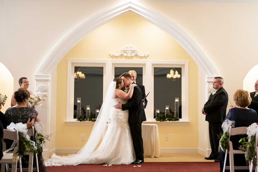 bride and groom kissing during a prayer in the chapel at Hudson Manor