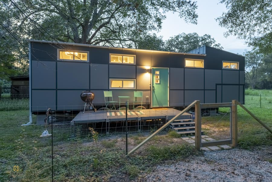 early evening shot of a teal and grey tiny house