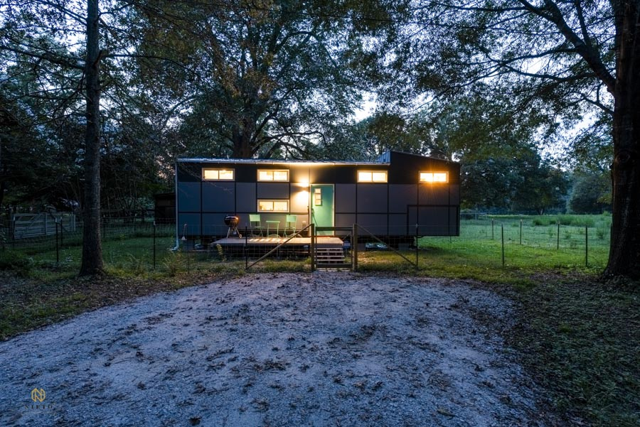 front shot of a tiny house at night with a gravel lot in front