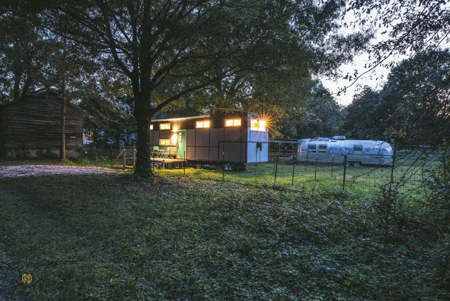 wide shot of tiny house at night in a rural area
