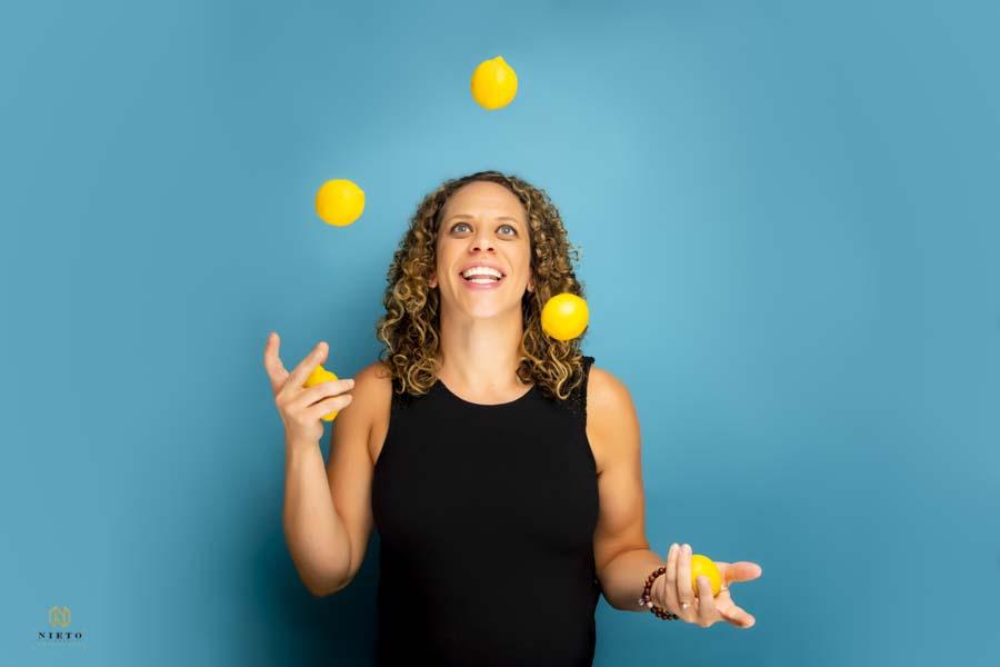 woman juggling lemons on a blue background