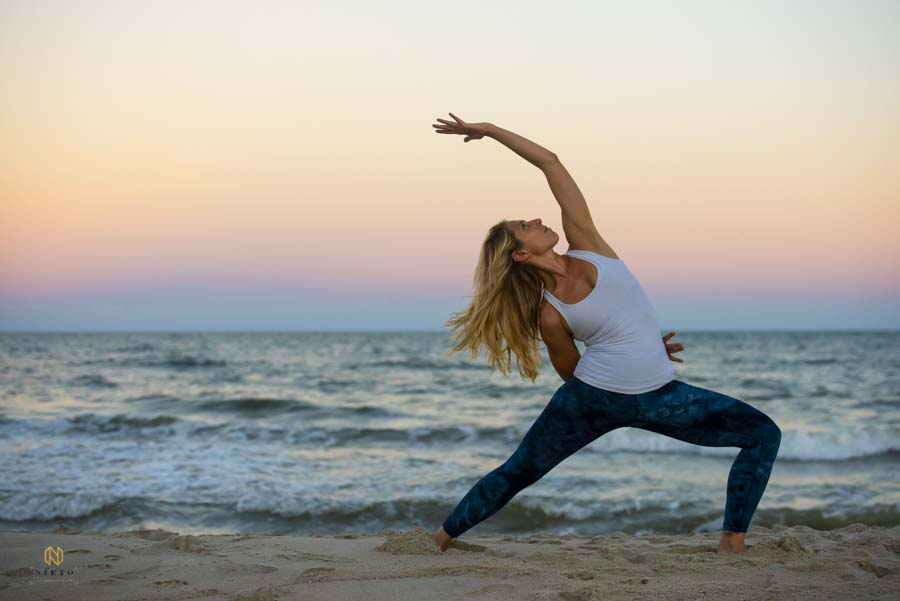 woman doing yoga pose on the beach at sunset