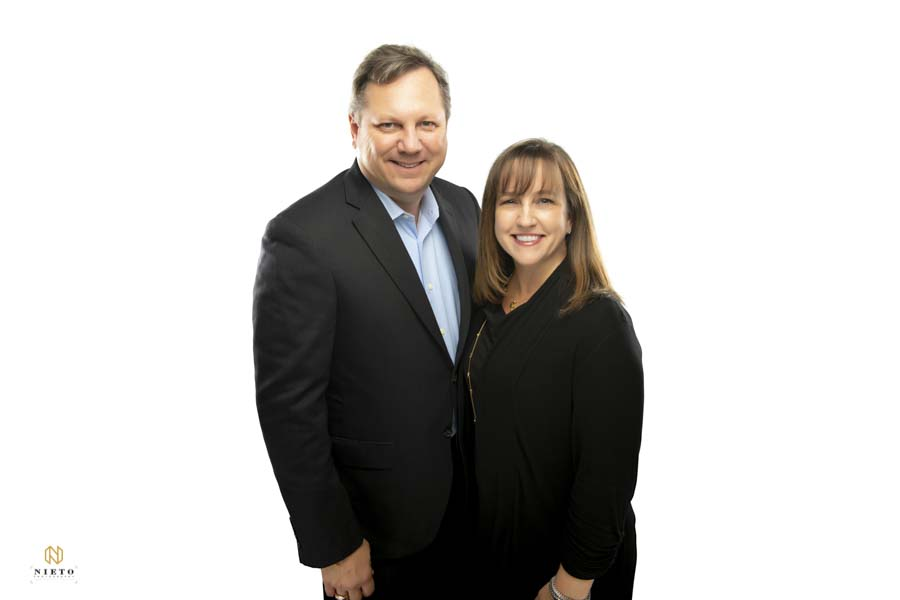 Couple smiling for headshot against a white background