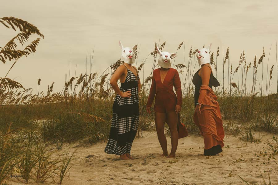 three women standing in a sand dune with white rabbit mask on