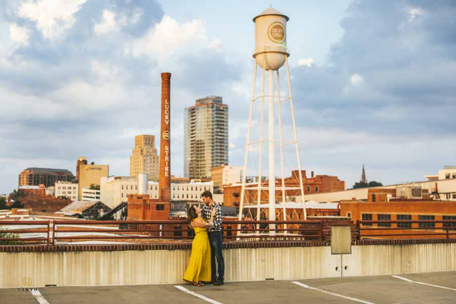 couple talking to each other on the parking deck of the American Tobacco Campus posing for their engagement session