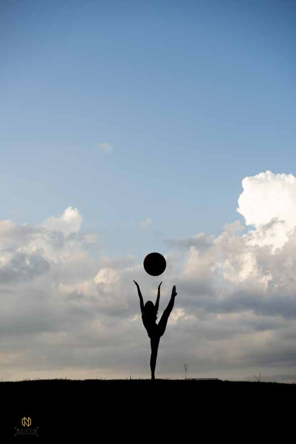woman silhouetted against the sky as she dances with a ball