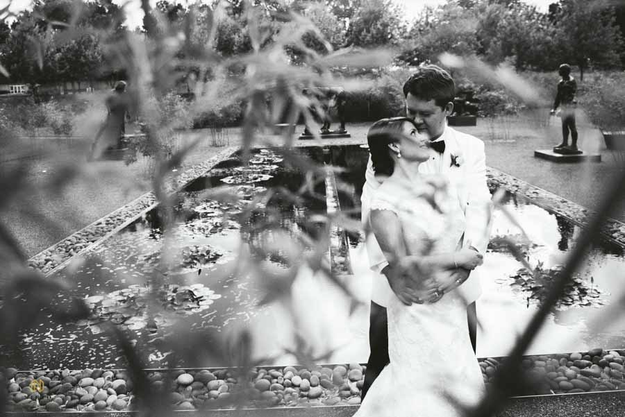 black and white image of a bride and groom hugging infant of the reflecting pond at the NC Museum of Art