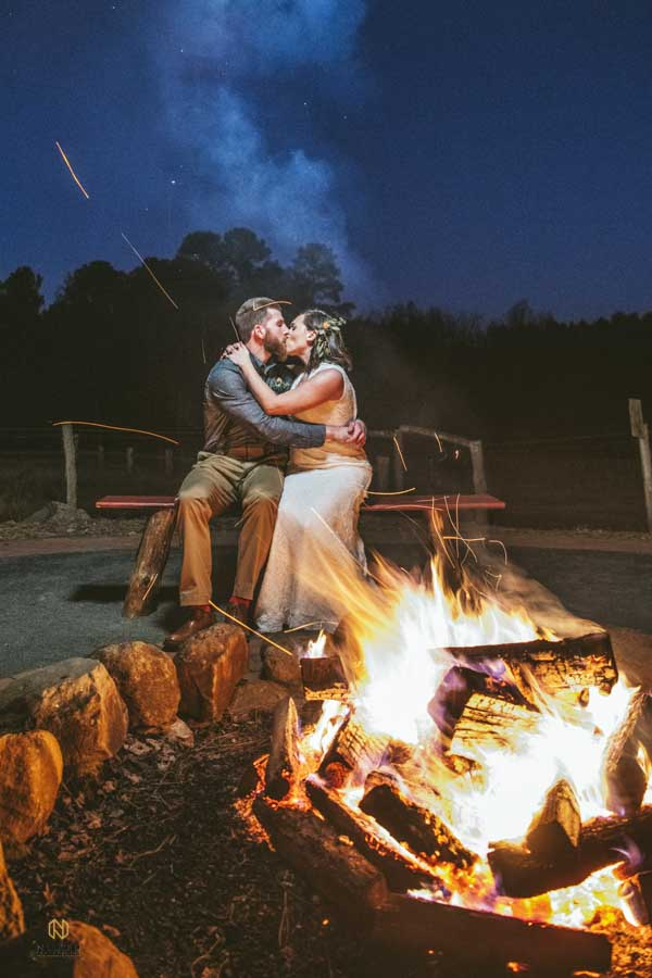 couple kissing in front of the fire pit at Cedar Grove Acres at night