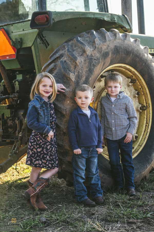 a little girl and two boys leaning up against a John Deere tractor tire posing for a portrait