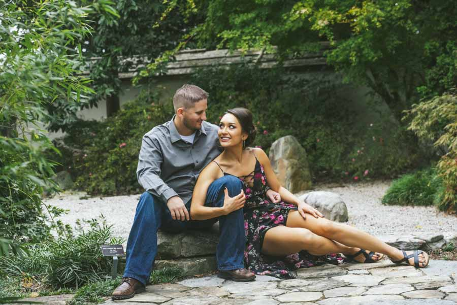 couple smiling at each other as they pose for their Raleigh engagement portrait