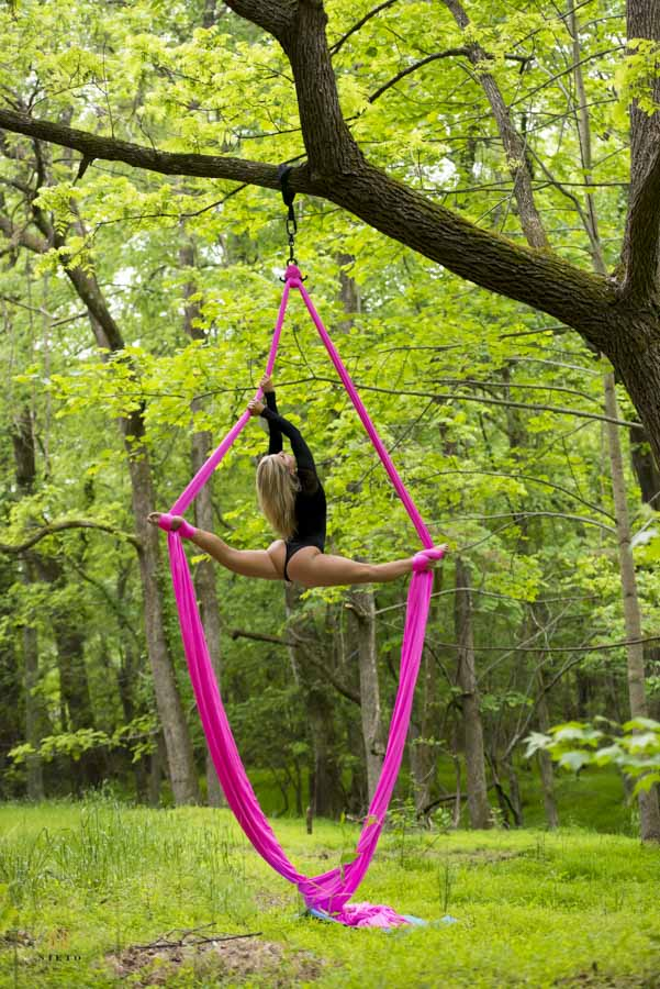 woman on ariel silks in the middle of the woods posing for a fitness portrait