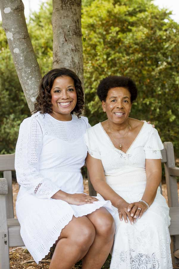mother and daughter sitting together smiling for their portrait in Raleigh