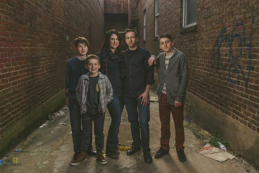 family of five in a downtown alley in Raleigh posing for their portrait