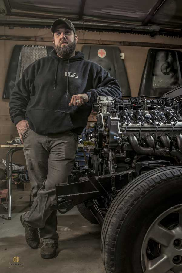 man leaning against a car engine