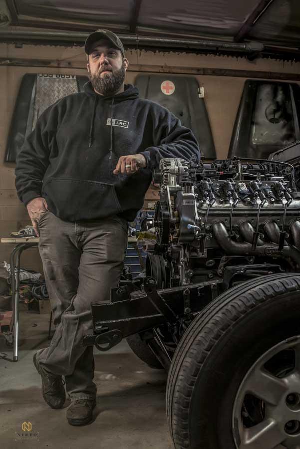 man leaning against a car engine