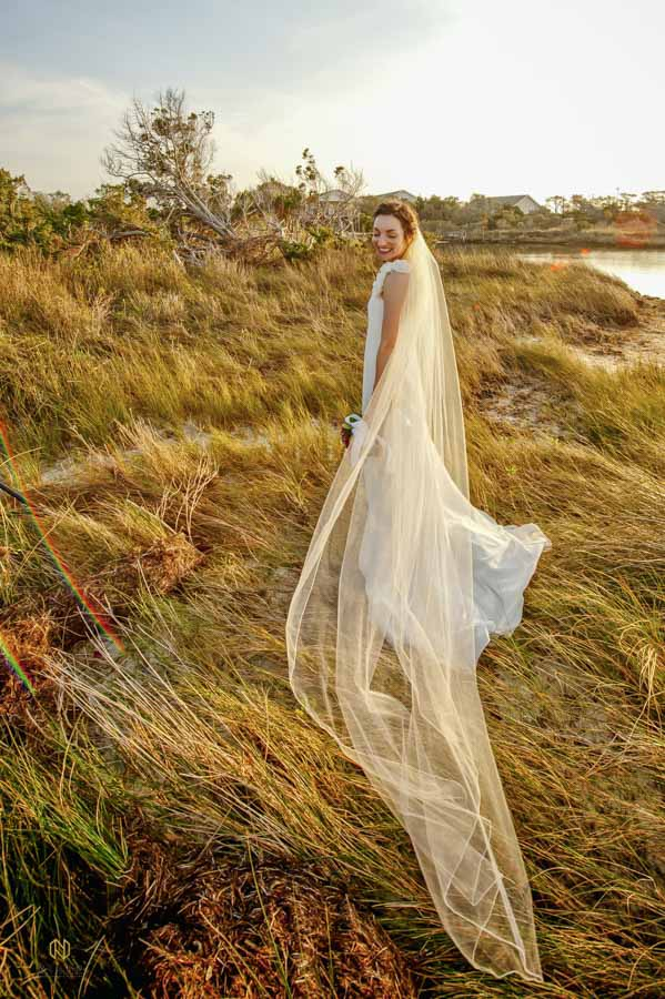 bride smiling as her veil blows in the wind while she stands in sea grass in the OBX