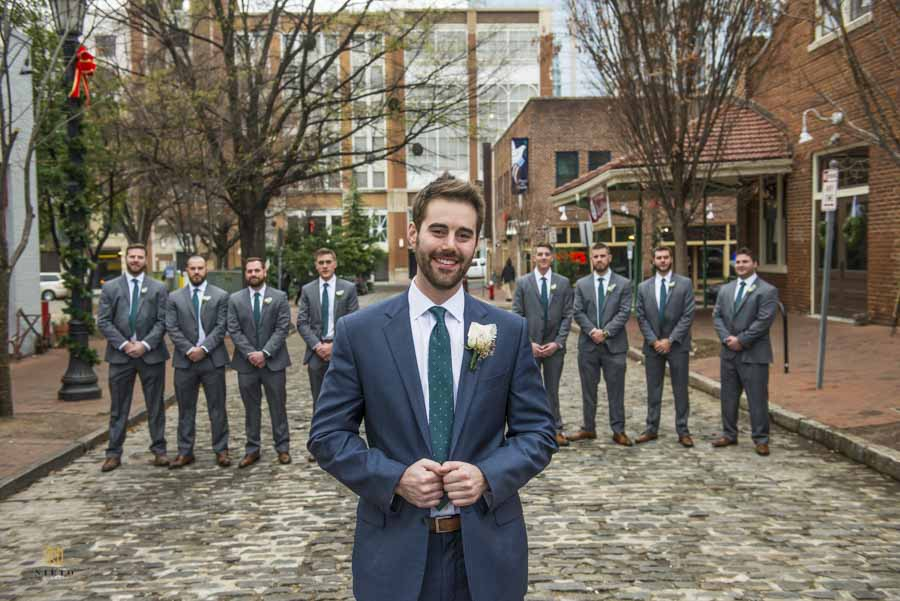 groom smiling for his portrait with his groomsmen behind him at Market Hall