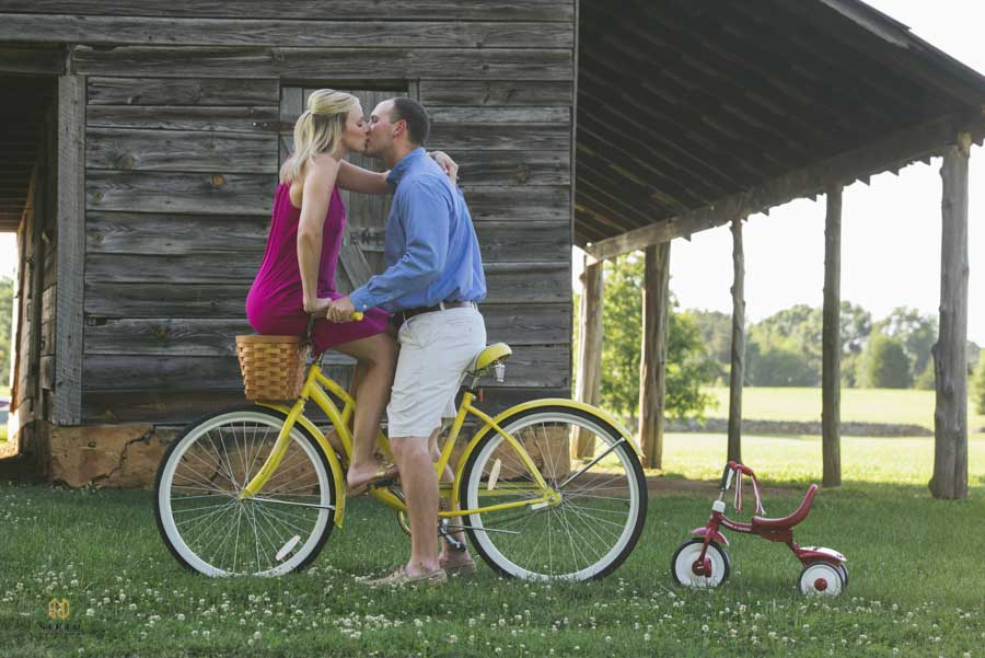 couple on a yellow bicycle kissing with a small tricycle behind the bike