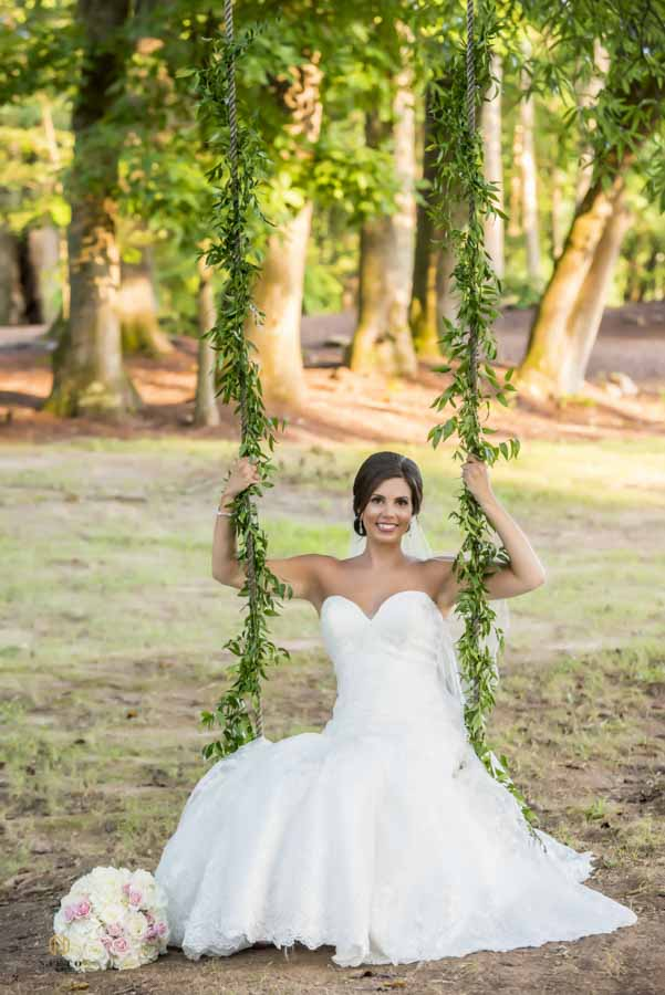 Bride sitting in a swing posing for her bridal portrait at Chapel in the Woods