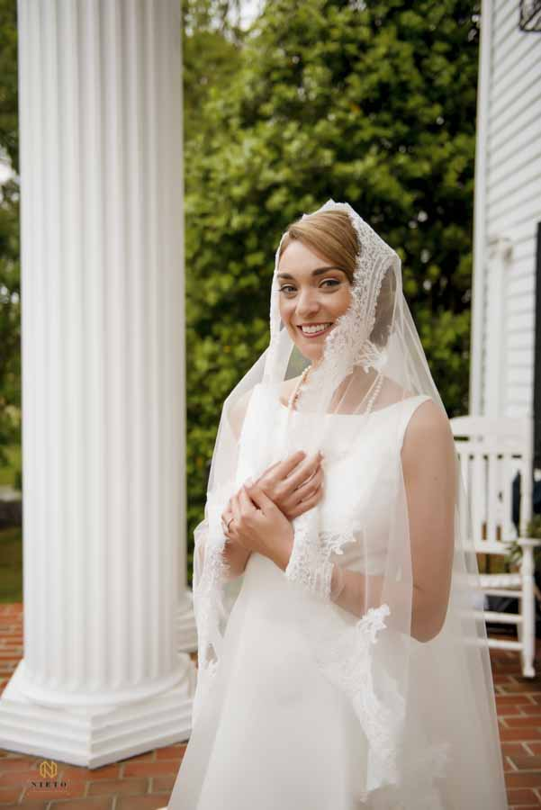 bride posing and smiling in her wedding veil on the front porch of the Hudson Manor
