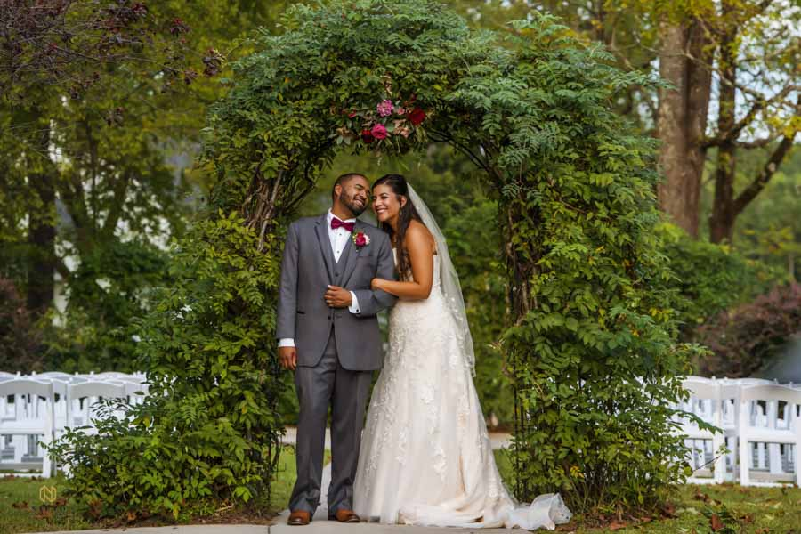bride and groom smiling together as the stand under the green arbor at The Hudson Manor in Louisburg NC