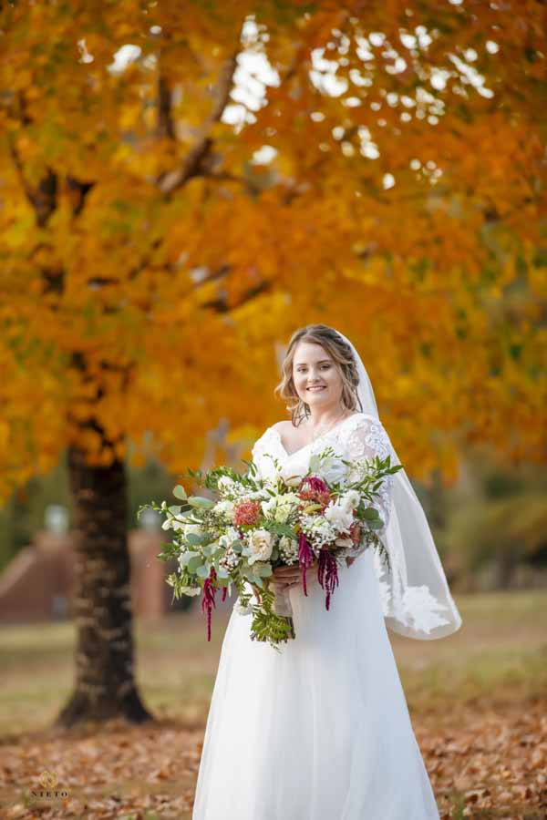 bride smiling as she holds her flowers and stands in front of a orange tree at the Hudson Manor