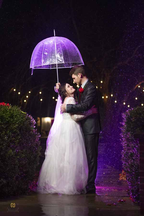 bride and groom hugging as the stand in the rain under and umbrella at night at the Hudson Manor
