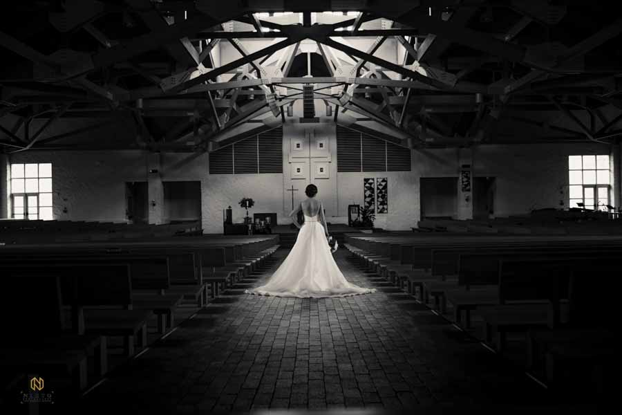 black and white image of a bride posing in the middle of a church aisle for her bridal portrait