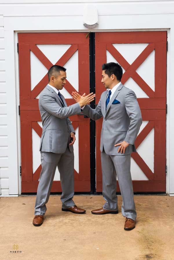 groom and his best man slapping hands together while taking a portrait