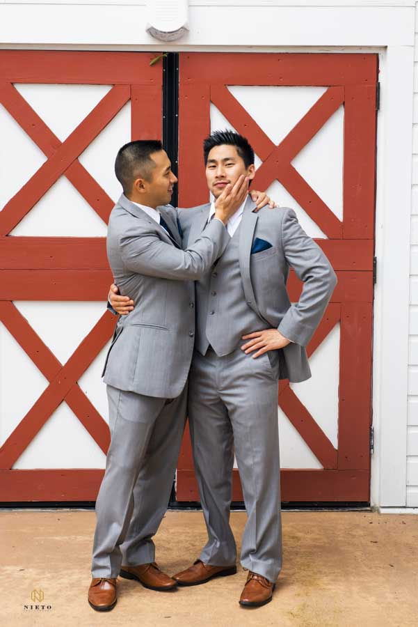 groom being caressed on the cheek by his best man as they pose for a wedding portrait