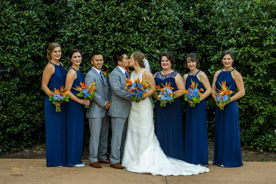 bridal party portrait with bride and groom kissing after their wedding ceremony