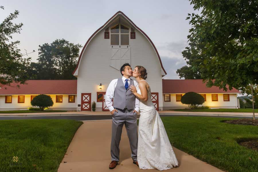 bride kissing the groom on the cheek in front of the barn at Winmock at Kinderton