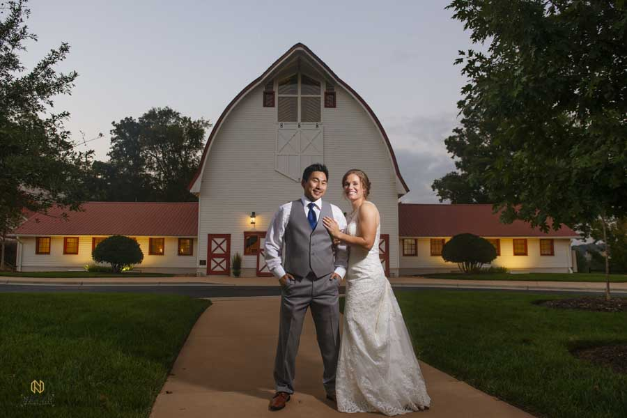 bride and groom posing for the camera in front of the Barn at Winmock at Kinderton