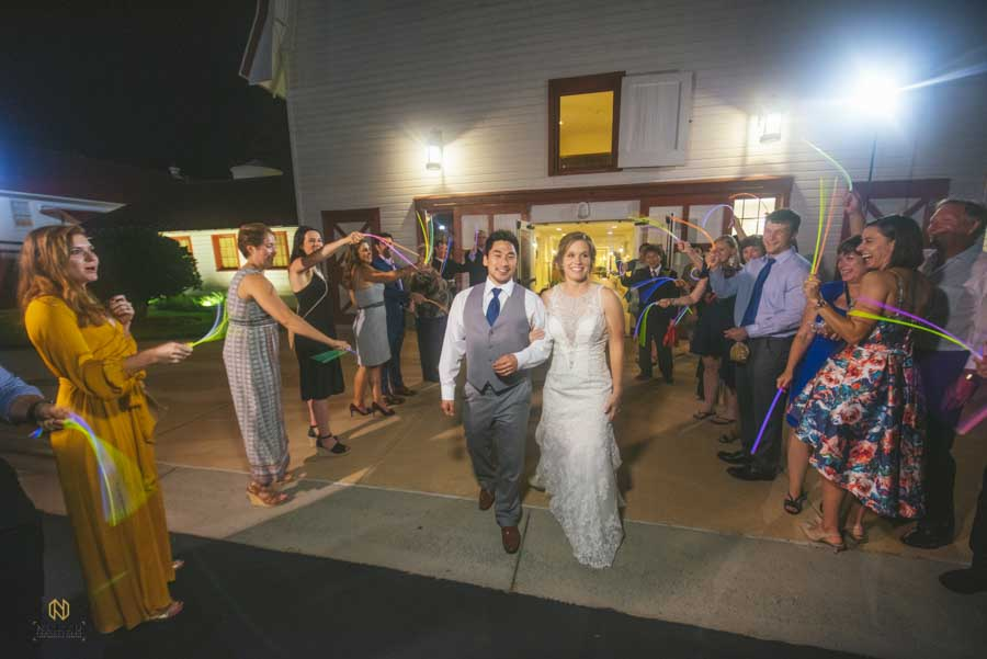 bride and groom locked arm in arm as they walk out of the barn at Winmock at their glow stick exit