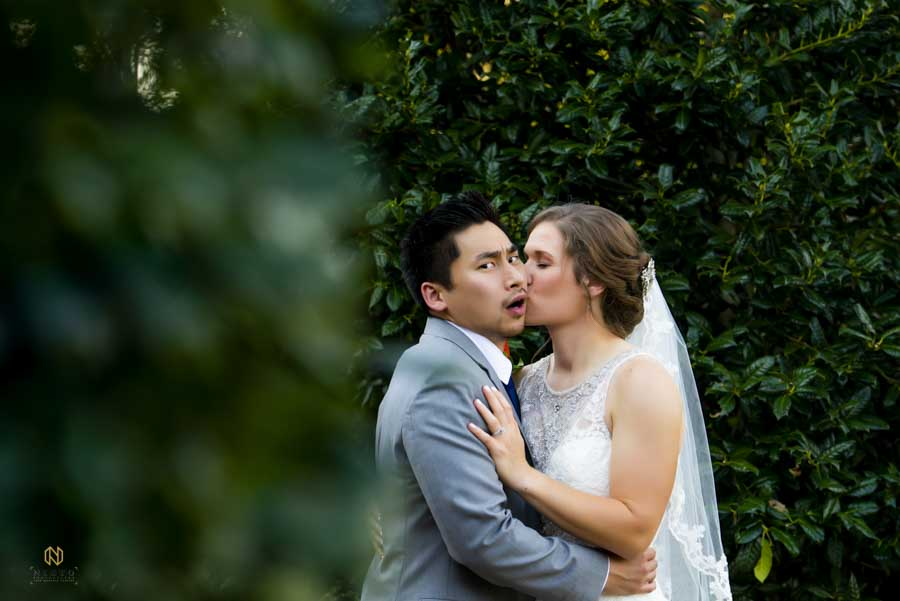 groom looking shocked as the bride kisses him on the cheek outside of Winmock wedding venue
