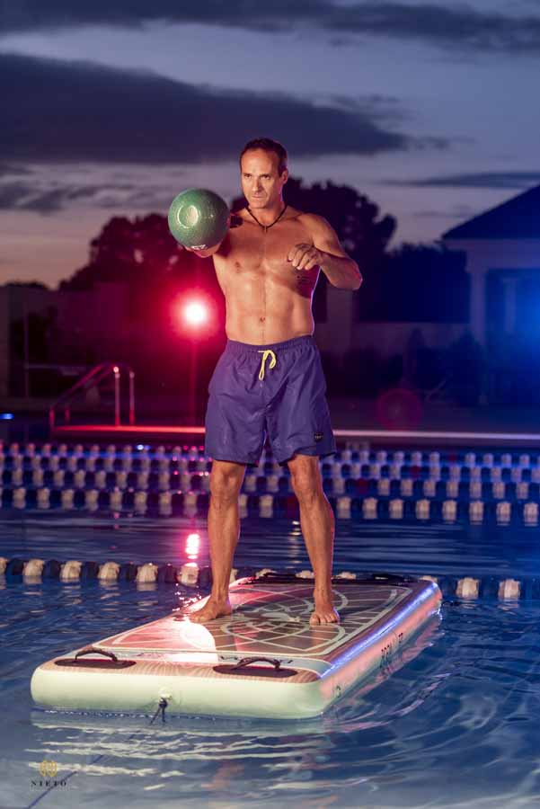 man on yoga board in a pool working out with a kettle bell in Raleigh
