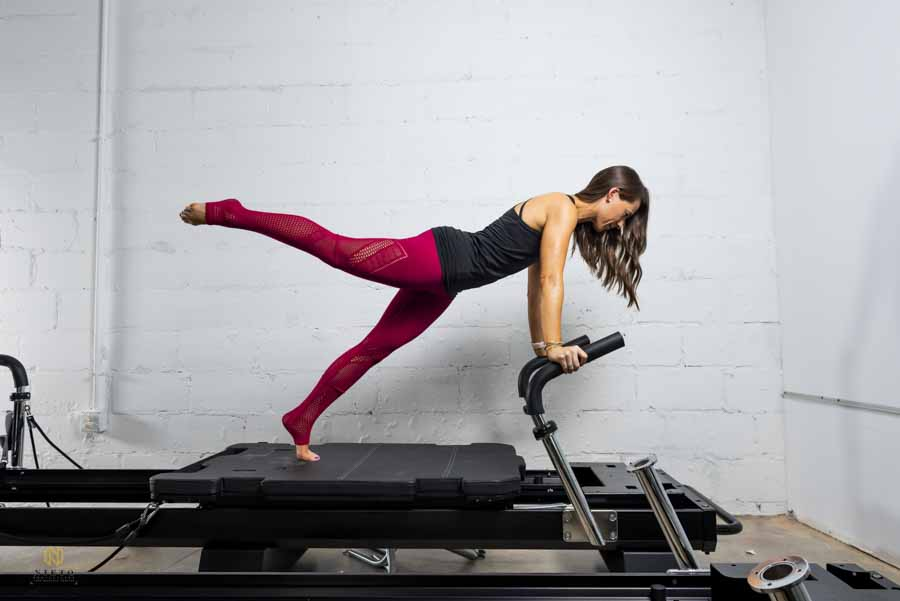 woman in red yoga pants working out doing pilates
