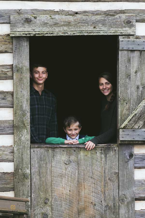there siblings smiling for their family portrait while standing in an open window